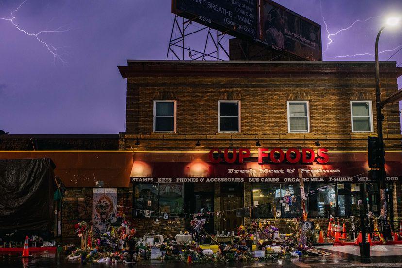 La fachada de Cup Foods, la tienda donde tuvo lugar el incidente con un billete falso que provocó el arresto mortal de George Floyd, rodeada de flores y mensajes la noche del pasado 5 de abril.BRANDON BELL / AFP